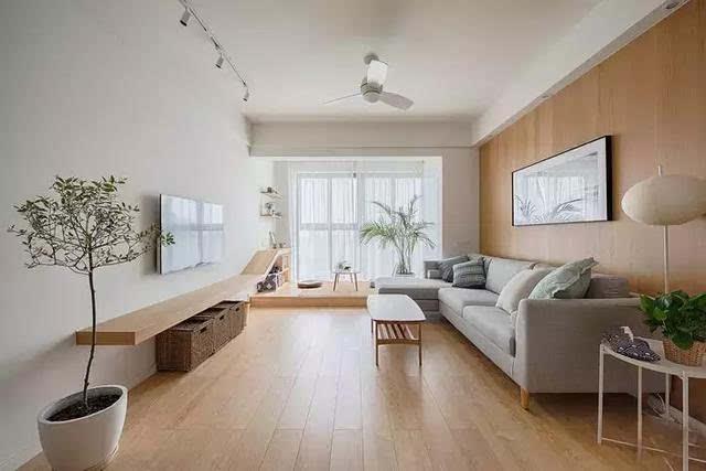 温润的木地板和木饰面沙发背景墙为客厅定下了基调,点缀其中的几株