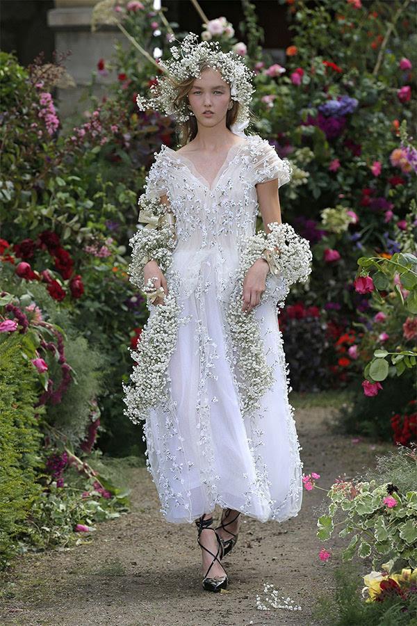 也是戴着以鲜花所做成的饰品,模特儿以纯白色的满天星作装饰和花冠,不图片