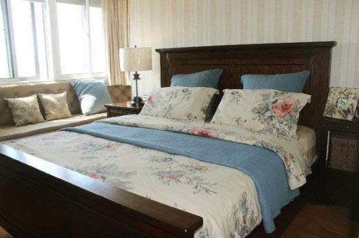 主卧室的墙面采用条纹壁纸,营造出浓浓的美式风范,深棕色的实木床架