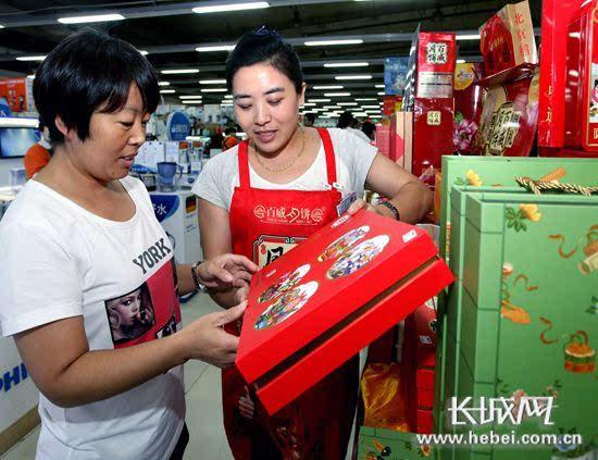 省会北国超市裕华店促销员为市民介绍一款礼盒月饼. 记者 任光阳 摄图片