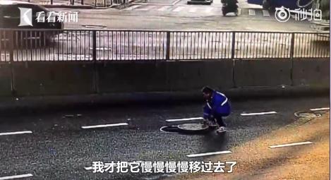 快递小哥跑向车流密集的马路中间 推回窨井盖