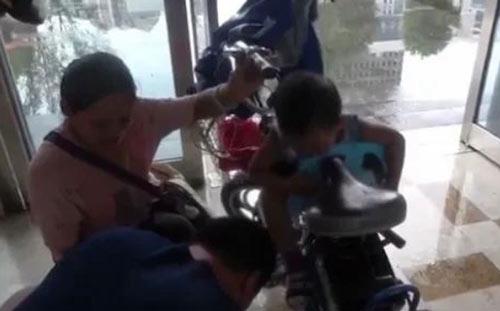 妈妈骑电动车躲雨,宝宝贪玩踏板意外卡脚